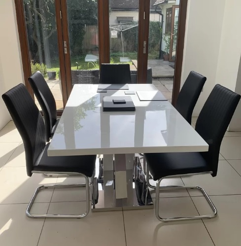 A white high gloss dining table with dark chairs to add colour