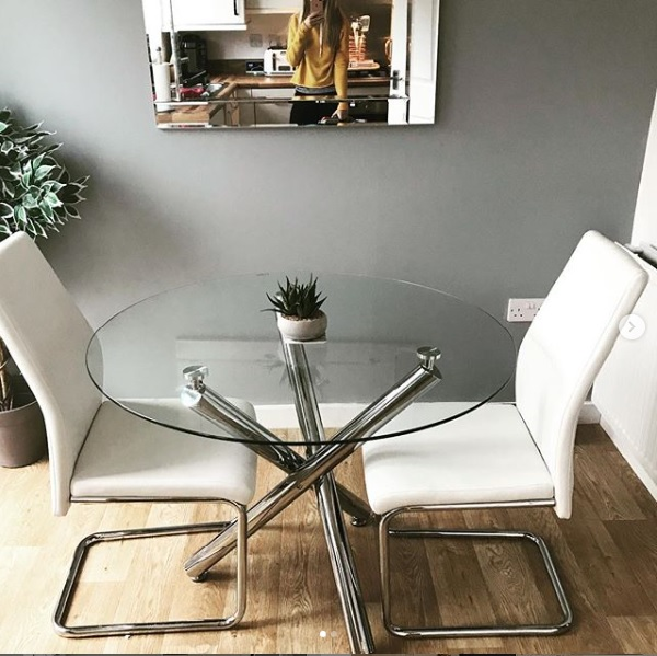 A glass and chrome dining table making a dining room feel bigger