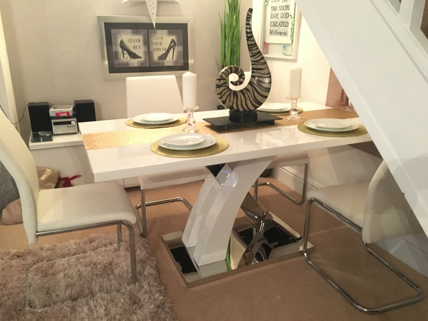 A white high gloss dining table with cream chairs and a coloured rug