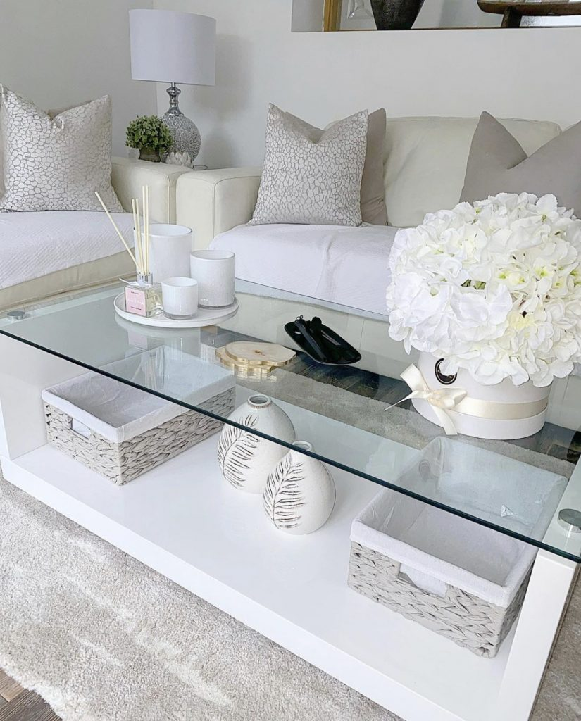 A white and cream living room space with a decorated coffee table