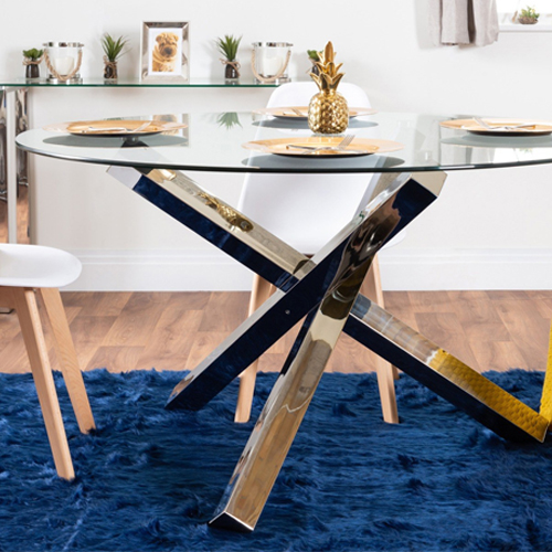chrome leg dining table with a glass top on a navy blue rug