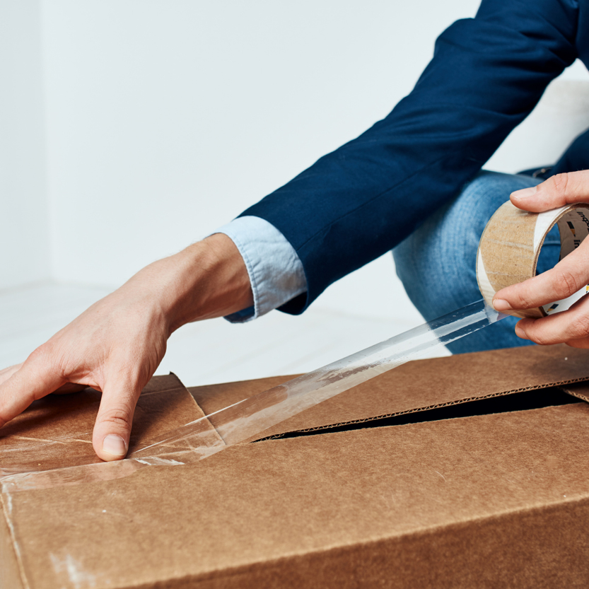 Image of a person packing sealing a packing box. declutter to prepare your home for sale