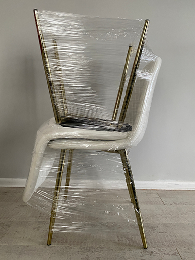Two dining chairs wrapped together will help protect them when you're packing to move house.